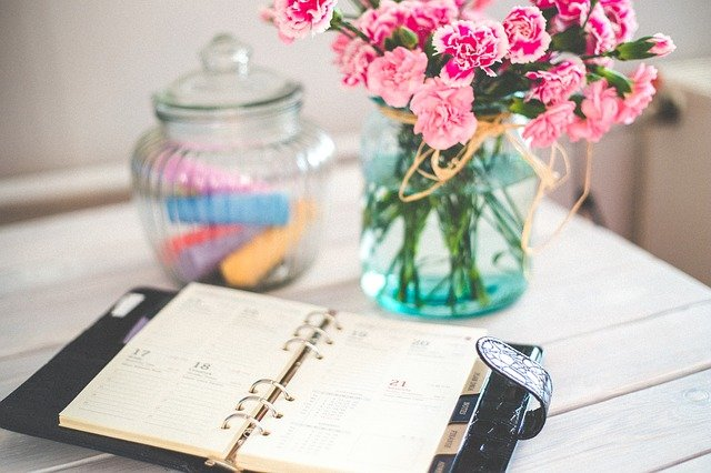 picture of a planner on a desk next to a vase of flowers
